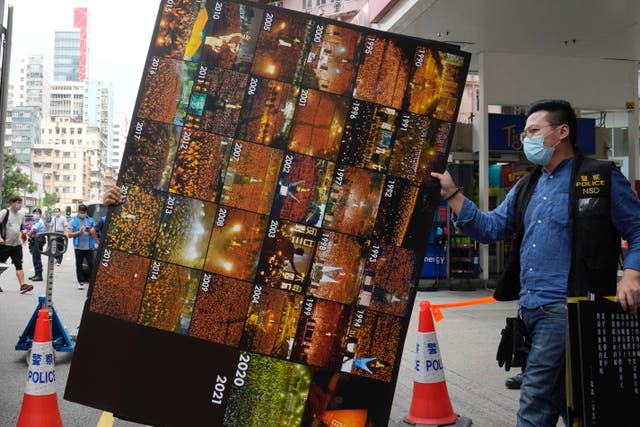 <p>Police remove as evidence pictures of the annual candlelight vigil for Tiananmen Square victims from the June 4th Museum last week </p>