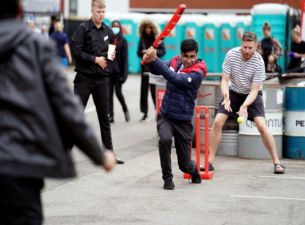 Fans play cricket outside of Old Trafford after the match was cancelled (Martin Rickett/PA)