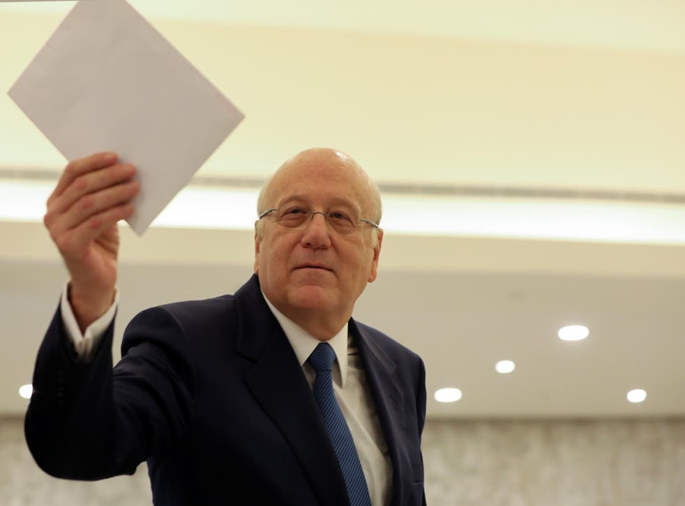 <p>Lebanon's prime minister Najib Mikati holds the cabinet list after meeting with the country's president Michel Aoun at the presidential palace in Baabda, Lebanon</p>
