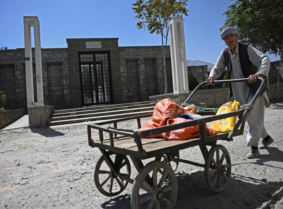 <p>A man pushes his handcart past the main entrance of the closed National Museum in Kabul on Wednesday </p>