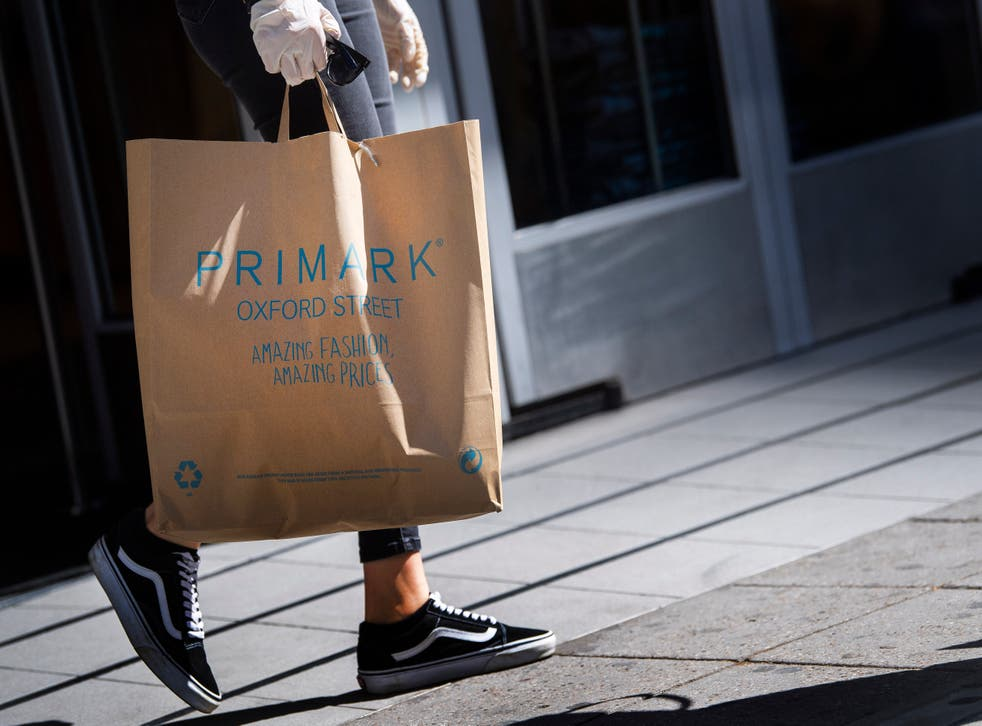 A customer carries bags of shopping as they leave Primark in Oxford Street (Victoria Jones/PA)