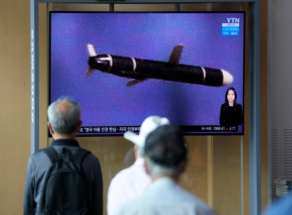 <p>Seoul residents watch a  news programme featuring a North Korean photo captioned, 'North Korea's long-range cruise missiles tests' </p>