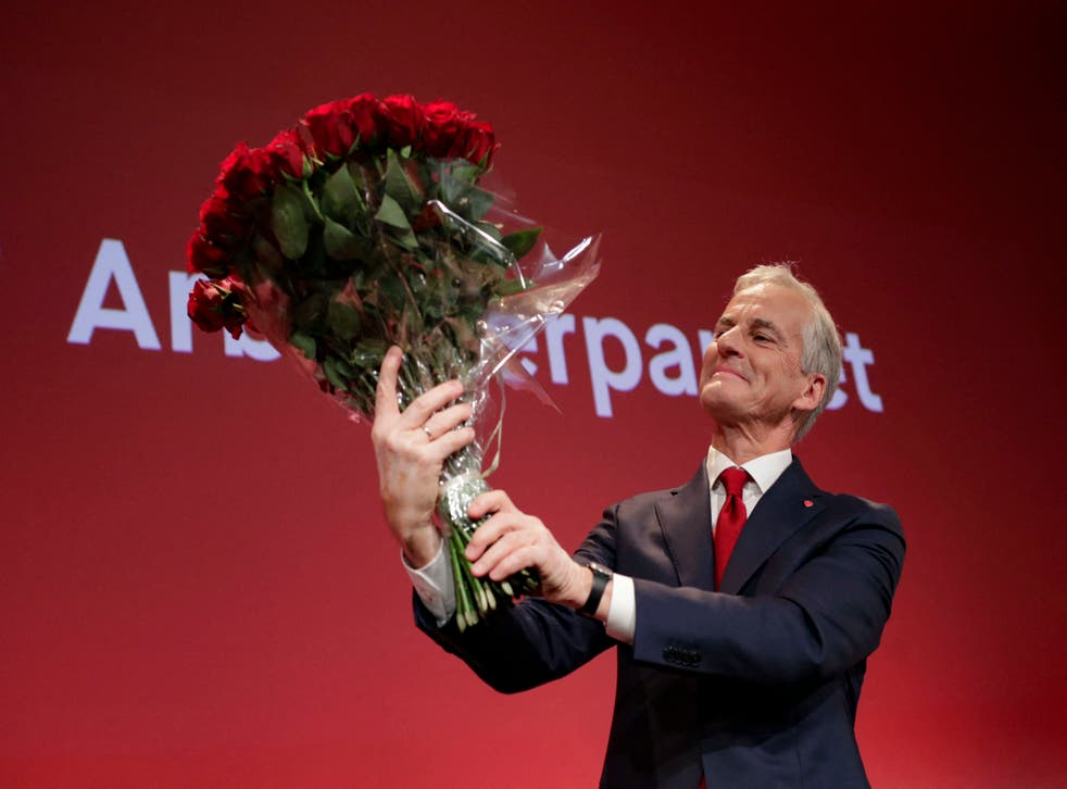 <p>Labour leader Jonas Gahr Store holds a bouquet of red roses after the results of the election</p>