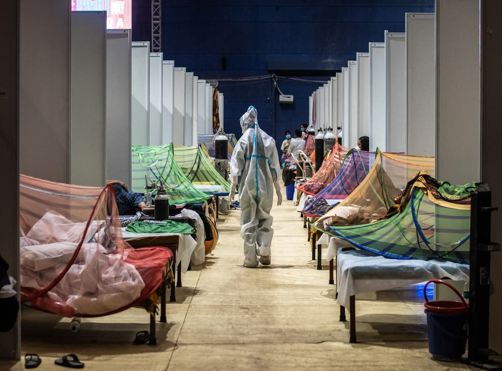 <p>A medical worker in PPE observes Covid-19 patients inside a makeshift care facility in a sports stadium at the Commonwealth Games Village in Delhi</p>