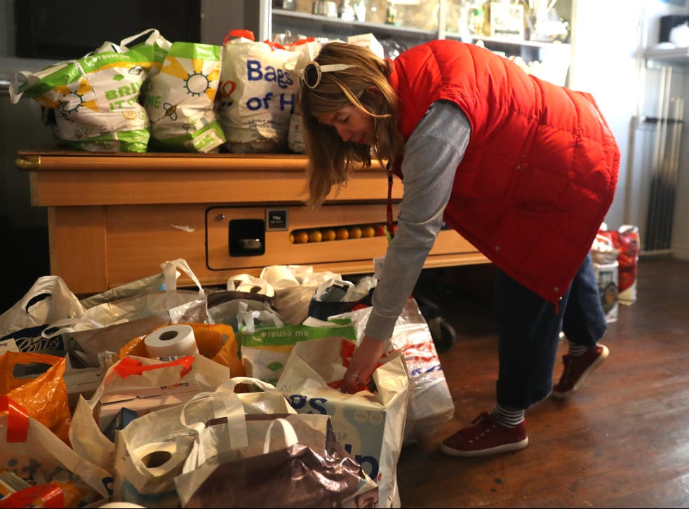 <p>A school teacher picks up food bags for her school at a food bank in Northampton during the first national lockdown</p>
