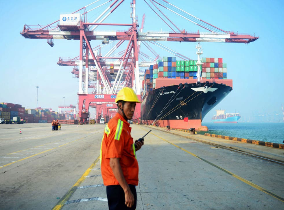 <p>A Chinese worker looks on as a cargo ship is loaded at a port in Qingdao, eastern China's Shandong province on 13 July 2017. </p>