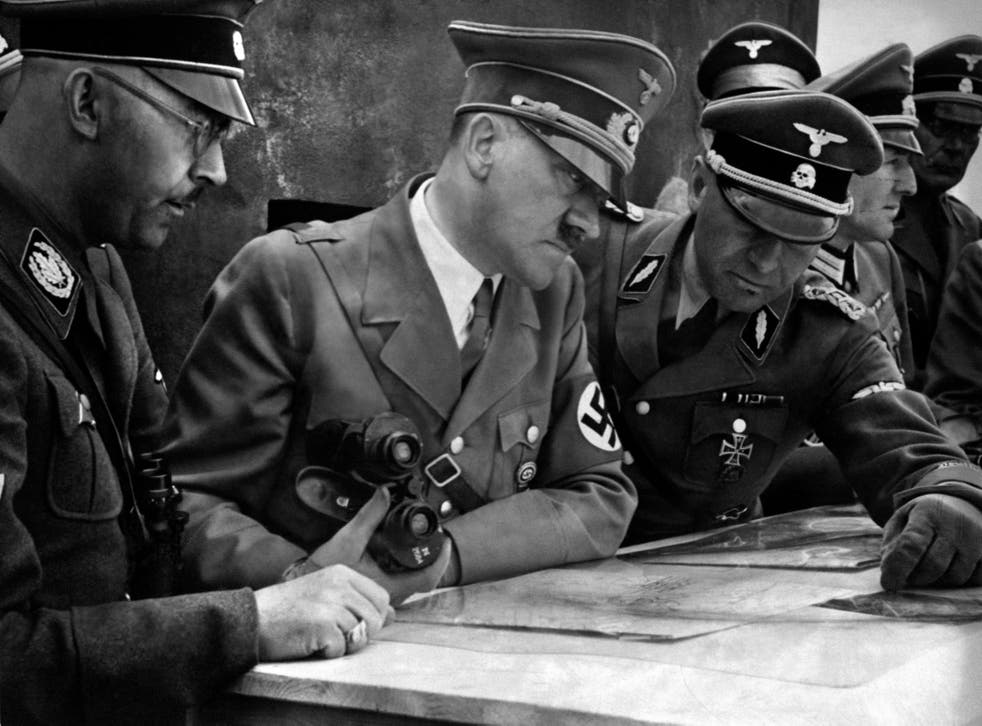 <p>A picture dated 1939 shows German Nazi Chancellor and dictator Adolf Hitler (C) consulting a geographical survey map with his general staff including Heinrich Himmler (L) and Martin Bormann (R) at an unlocated place during World War II</p>