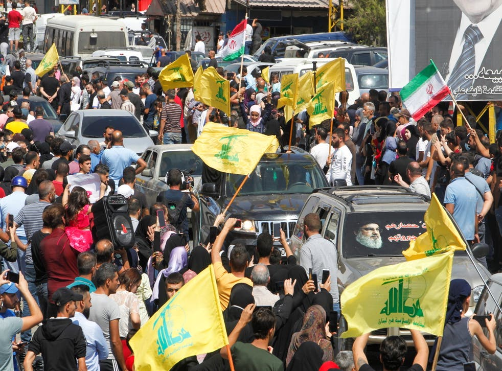 <p>People wave Hezbollah and Iranian flags as a convoy of tanker trucks carrying Iranian fuel drives through the streets </p>