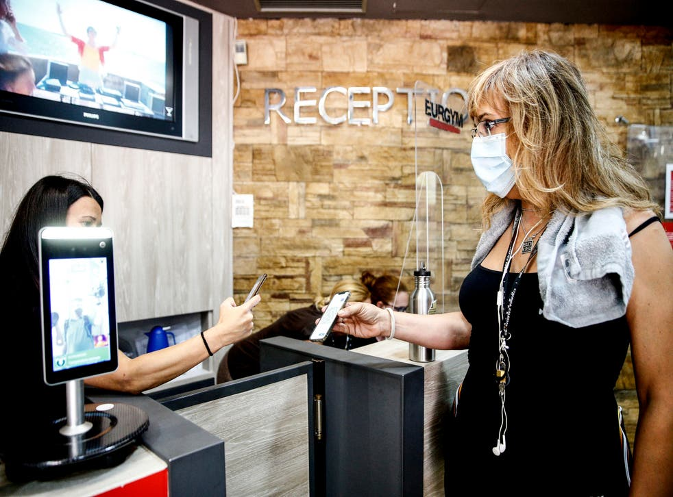 <p>File: A customer has her green pass checked at the entrance of a gym in Rome</p>