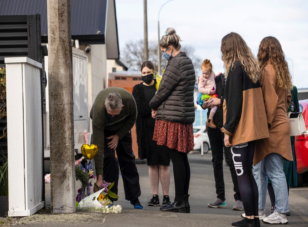 <p>People lay flowers outside of a house where three children were found dead </p>
