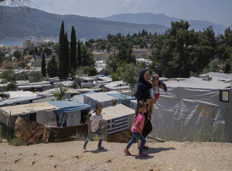 <p>An Afghan woman with her three children walk outside the perimeter of the refugee camp at the port of Vathy on the eastern Aegean island of Samos, Greece, on Friday, 11 June </p>