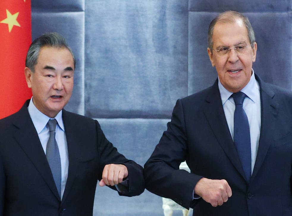 <p>China's Foreign Minister Wang Yi (L) and his Russian counterpart Sergei Lavrov bump elbows as they meet for talks</p>