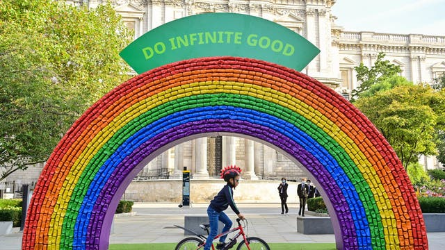 Hugo, 7, from London rides past a 4x7 metre rainbow arch, made entirely of recycled aluminium cans, which has been installed by recycling initiative 'Every Can Counts', in partnership with The City of London Corporation in front of St Paul's Cathedral in London, to encourage members of the public to recycle their drinks cans ahead of recycling week, which starts on 20 September