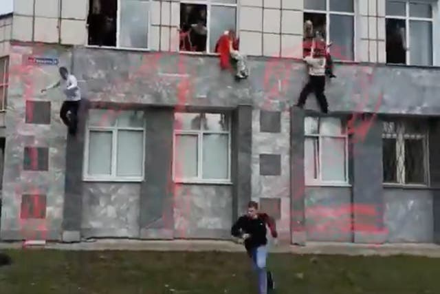 <p>Footage shows desperate students jumping from first floor windows of the building</p>