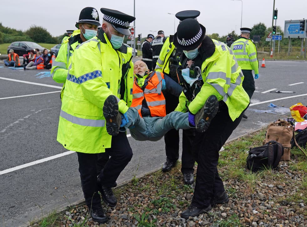 <p>Police officers carry away an Insulate Britain  protester who had glued himself to the highway at a slip road at Junction 4 of the A1(M), near Hatfield</p>