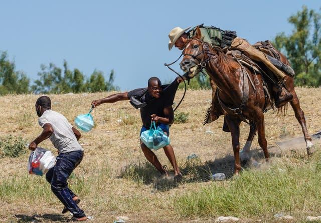 Un agente de la Patrulla Fronteriza de los Estados Unidos a caballo intenta evitar que un migrante haitiano ingrese a un campamento a orillas del Río Grande cerca del Puente Internacional Acuña del Río en Del Río, Texas