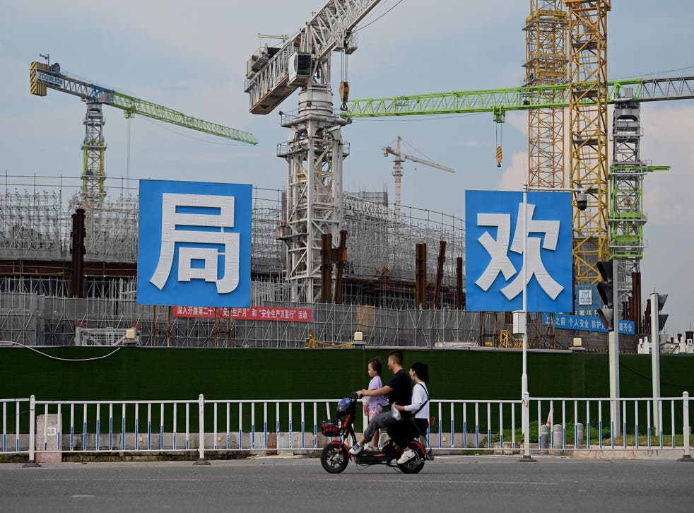 <p>People commute in front of the under-construction Guangzhou Evergrande football stadium in Guangzhou, China's southern Guangdong province </p>