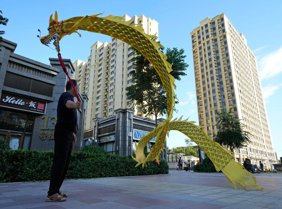 <p>A resident wields a cloth dragon outside the Evergrande Yujing Bay residential complex in Beijing, China</p>