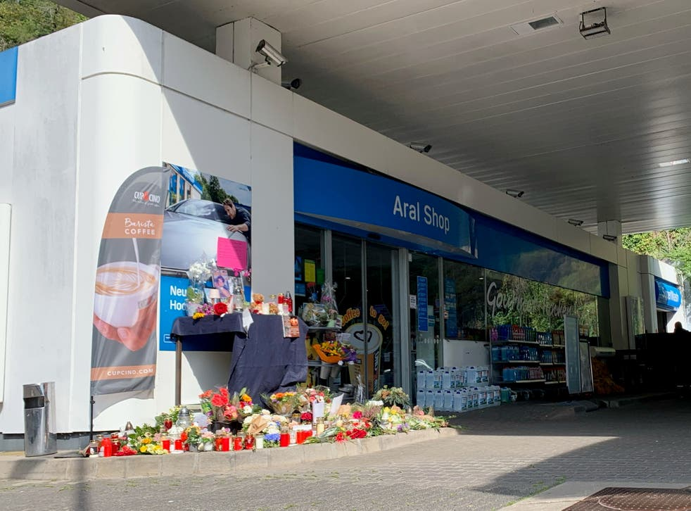 <p>Flowers are placed in front of petrol station in Idar-Oberstein, Germany, where a man has been killed</p>