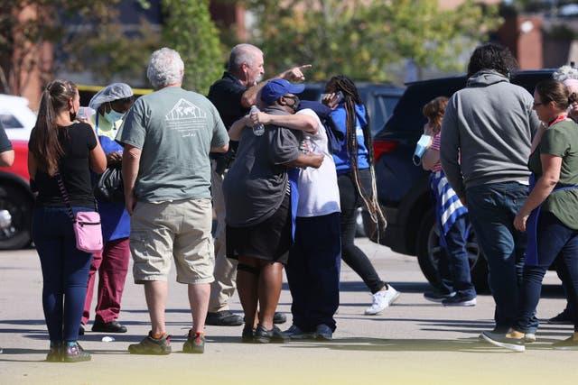 La gente se abraza mientras la policía responde a la escena de un tiroteo en una tienda de comestibles Kroger's en Collierville, Tennessee