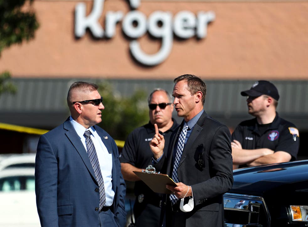 <p>Law enforcement officers confer at the scene following the shooting</p>