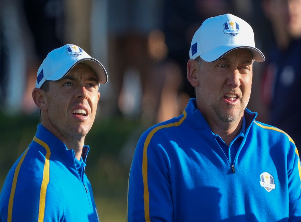 Rory McIlroy and Ian Poulter look over a shot on the second hole during their foursomes match at the Ryder Cup (Charlie Neibergall/AP)