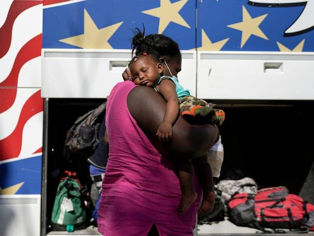 Una madre y su hijo se preparan para abordar un autobús lejos de la frontera entre Estados Unidos y México.