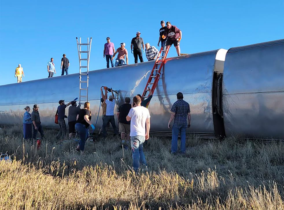 <p>People at the scene help to evacuate passengers from the Amtrak train, which derailed at 4pm on Saturday </p>