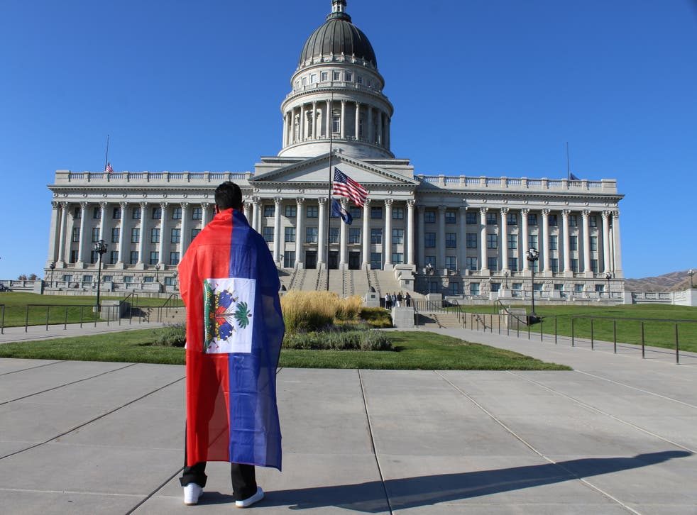 <p>A supporter of Haitian immigrant rights draped in the Caribbean country's flag stands in front of the Utah Capitol on Friday, Sept. 24.</p>