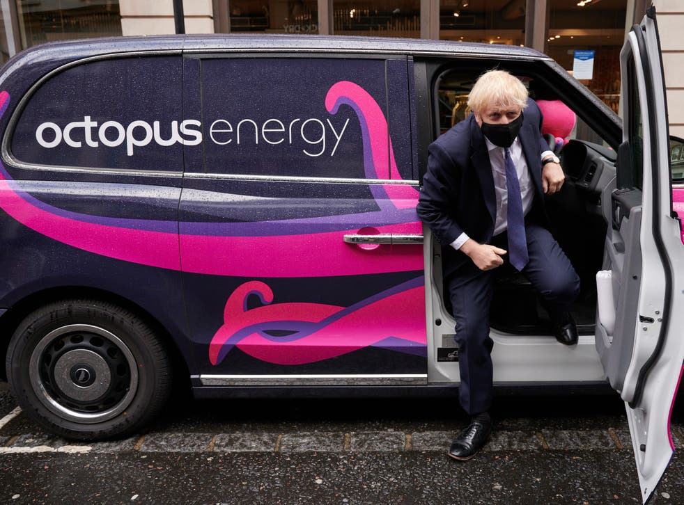 <p>The file photo from October 2020 shows Boris Johnson posing for photographs as he visits the headquarters of Octopus Energy</p>