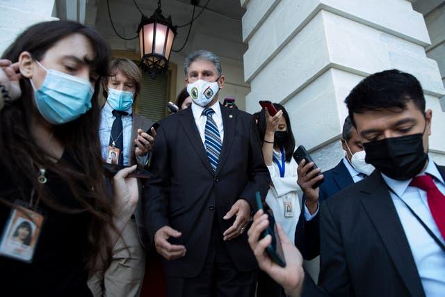El senador demócrata de West Virginia Joe Manchin (C) es seguido por miembros de los medios de comunicación después de salir de la cámara del Senado durante una votación de procedimiento sobre el aumento del límite de la deuda, en Capitol Hill en Washington, DC