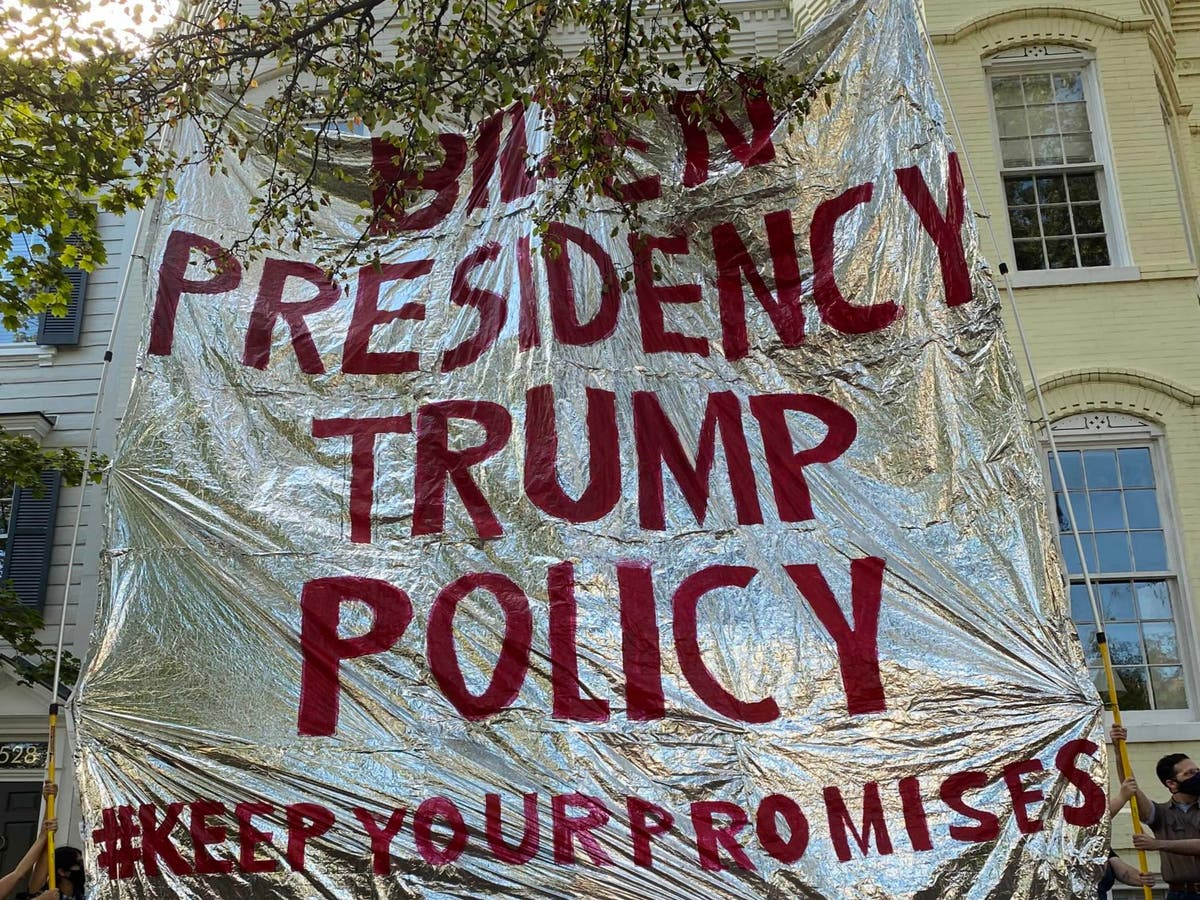Immigration protesters hold up giant foil blanket at DHS secretary's home accusing Biden of upholding Trump policies - independent