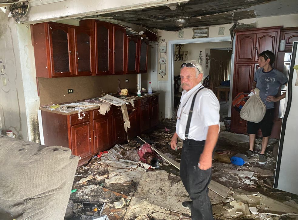 <p>Durle Blanchard and his son Louis examine the damage inside his home in Chauvin, Louisiana nearly one month after Hurricane Ida.</p>