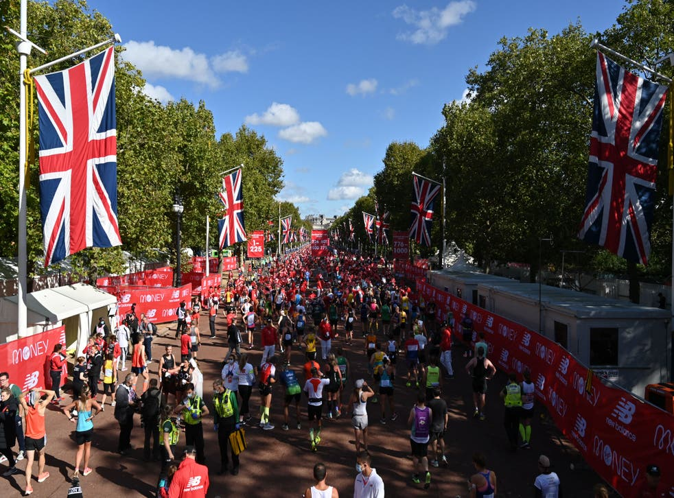 <p>Runners relax on the Mall after finishing the 2021 London Marathon</p>