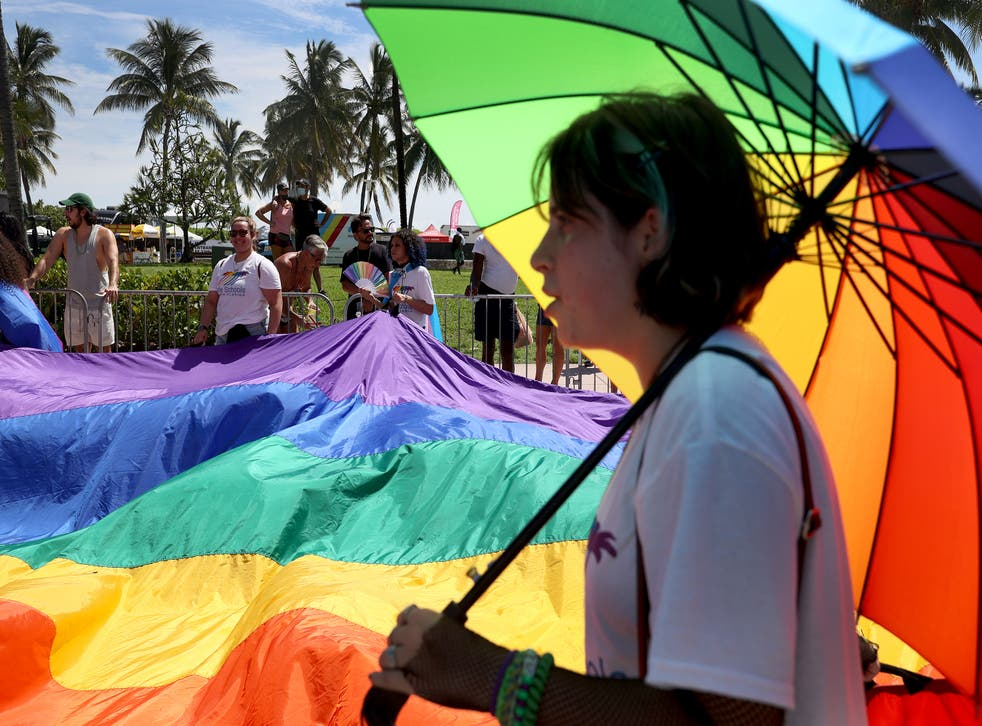 <p>People carry the rainbow flag as they participate in the Miami Beach Pride Parade along Ocean Drive on 19 September 2021 in Miami Beach, Florida</p>