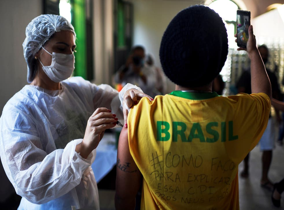 <p>File: A health worker administers a Covid vaccine dose to a resident as he takes a selfie, during mass vaccination at the Ilha Grande island, one of the most famous tourist spots in Rio de Janeiro state, Brazil</p>