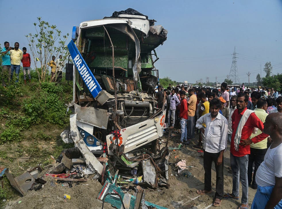 <p>People stand near the wreckage of a bus that collided with a truck in Barabanki district in Uttar Pradesh state, India</p>
