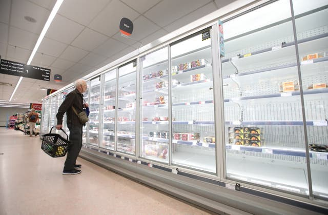 <p>A shopper looks at the empty shelves of a supermarket meat aisle</p>