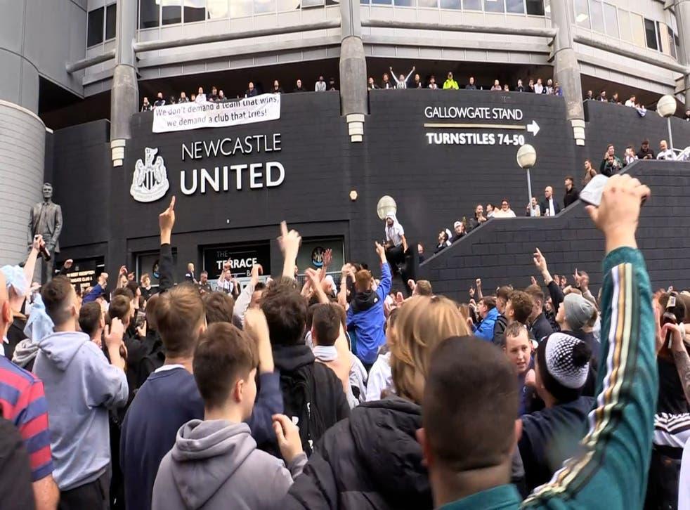 <p>Jubilant Newcastle fans celebrate the club's Saudi takeover outside the stadium</p>