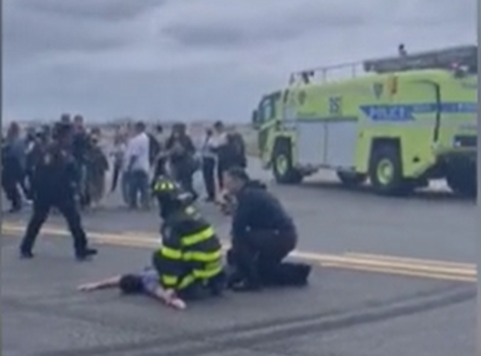 <p>The American Eagle passenger is pinned down by airport staff</p>