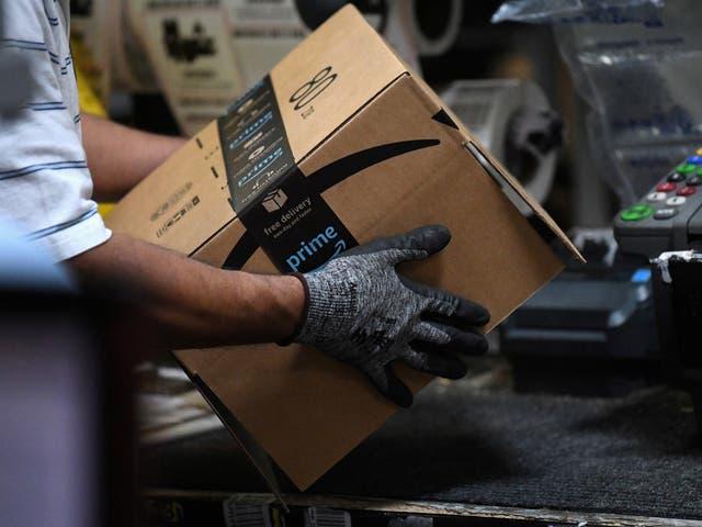 Trabajador ensambla una caja para su entrega en un almacén de Amazon