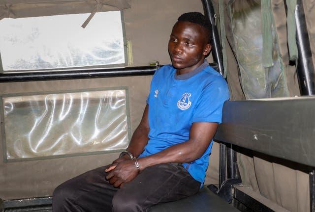 Masten Wanjala se sentó en la parte trasera de un camión de la policía que estaba siendo llevado por la policía para identificar la ubicación de los restos de la presunta víctima.