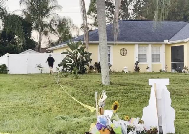 Chris Laundrie se lleva un cartel de protesta que se había plantado en su césped en North Port, Florida