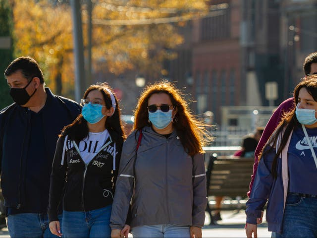 Un grupo de amigos caminando al aire libre con máscaras.