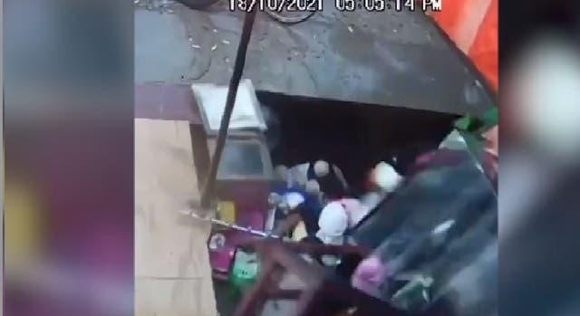 Captura de pantalla de un video de CCTV que muestra un enorme sumidero que se traga una tienda llena de clientes en el norte de la India