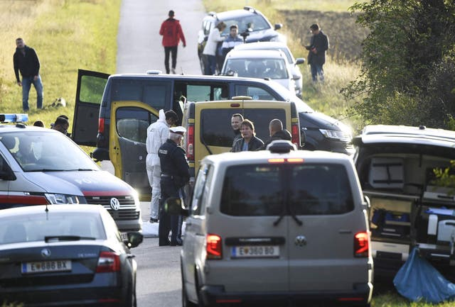 <p>Austrian police are seen near the Austrian-Hungarian border where two refugees were discovered dead inside the yellow van pictured. </p>