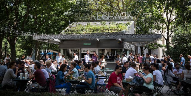 <p>People sit outside the original Shake Shack in Madison Square Park in New York City</p>