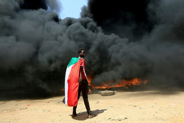 <p>A person wearing a Sudan flag stand in front of a burning pile of tyres during a protest against a return to military rule in Khartoum</p>