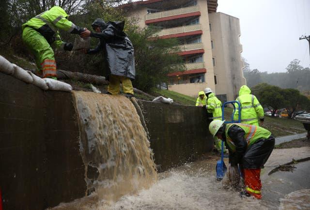 <p>Los trabajadores intentan desviar el agua hacia los desagües mientras la lluvia cae en Marin City, California. </p>