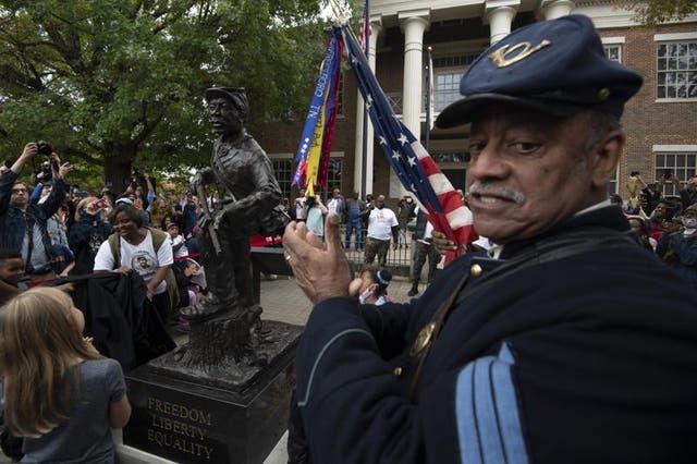 """<p>La estatua muestra a un soldado de pie con un pie sobre un tocón de árbol en descomposición, símbolo del final del """"árbol del dolor"""" que se usó para atar a las personas de color que fueron comerciadas y vendidas. </p>"""